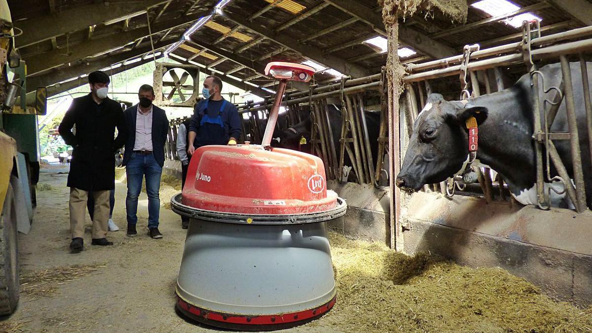 Por la izquierda, Borja Sánchez, José Ramón Feito y Manuel Álvarez Ron, ante un robot que acerca la comida a las vacas, ayer, en Tineo. | D. Á.