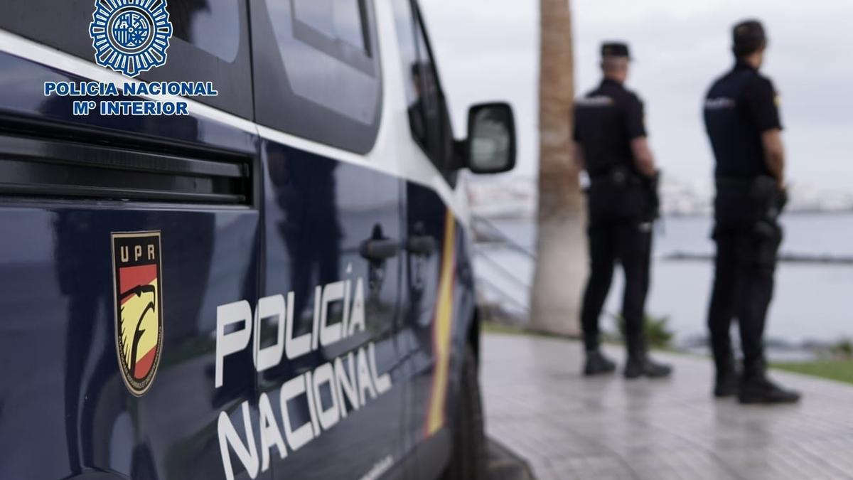 Agentes de la Policía Nacional junto a un coche patrulla.