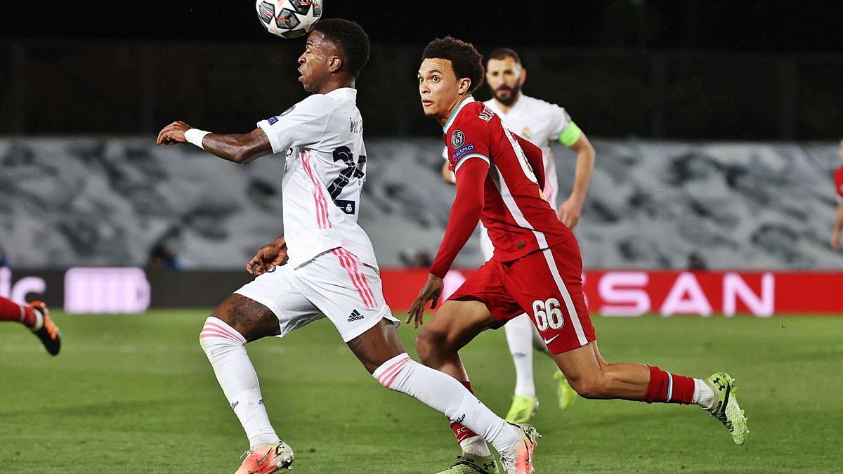 Vinicius corre y controla el balón perseguido por Alexander-Arnold en el Madrid-Liverpool disputado ayer en el Alfredo di Stefano.    // JUANJO MARTÍN