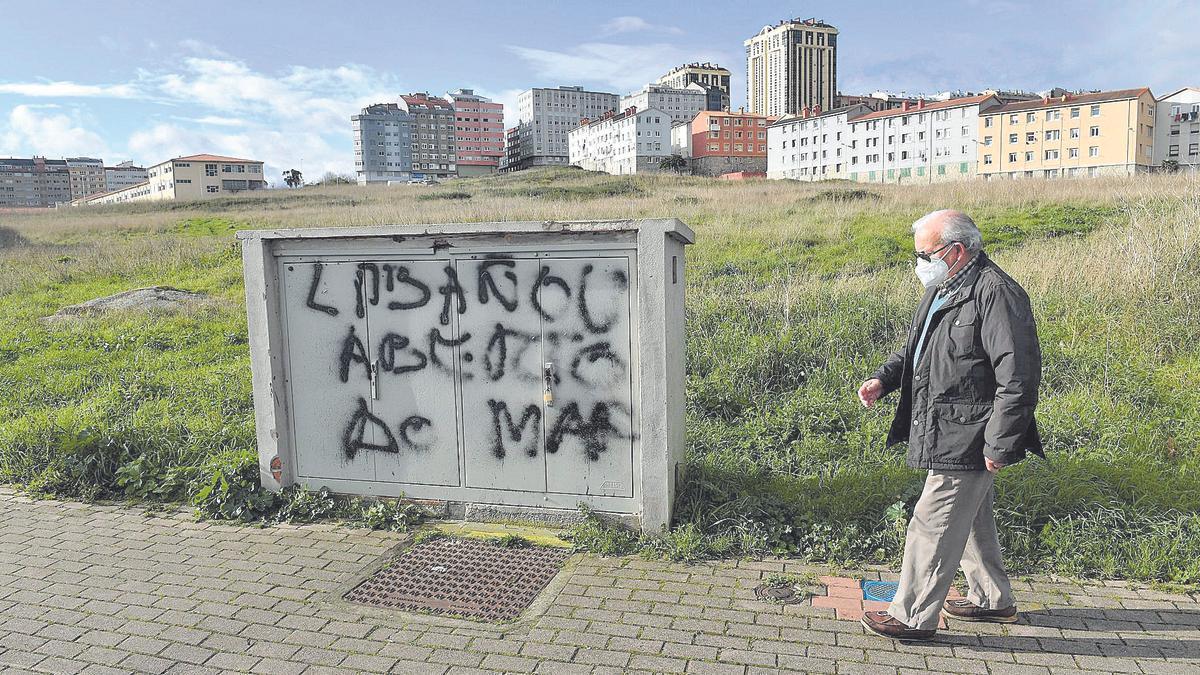 Un hombre pasa junto a los terrenos de As Percebeiras donde está proyectado un polígono residencial. | Víctor Echave