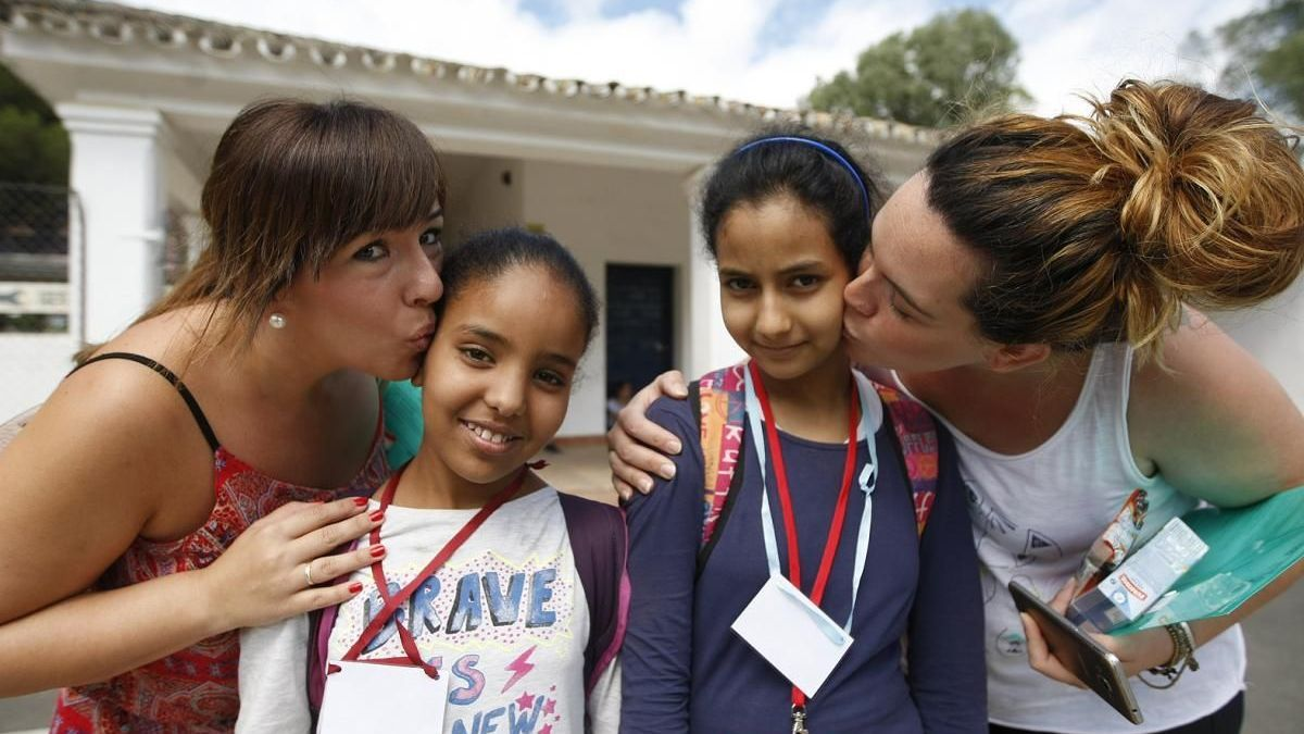 Dos madres de acogida besan a dos niñas saharauis recién llegadas, en una edición anterior.