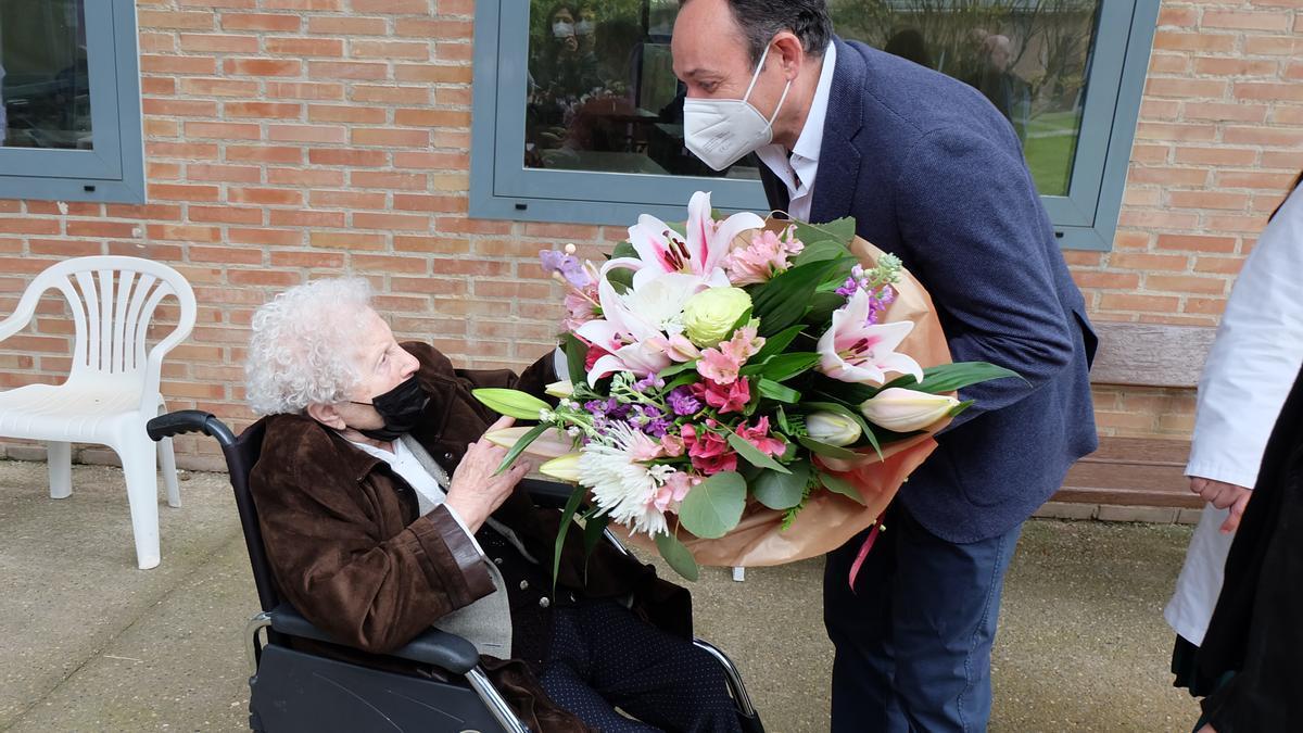 El alcalde turiasonense entrega un ramo de flores a la anciana, de 105 años.
