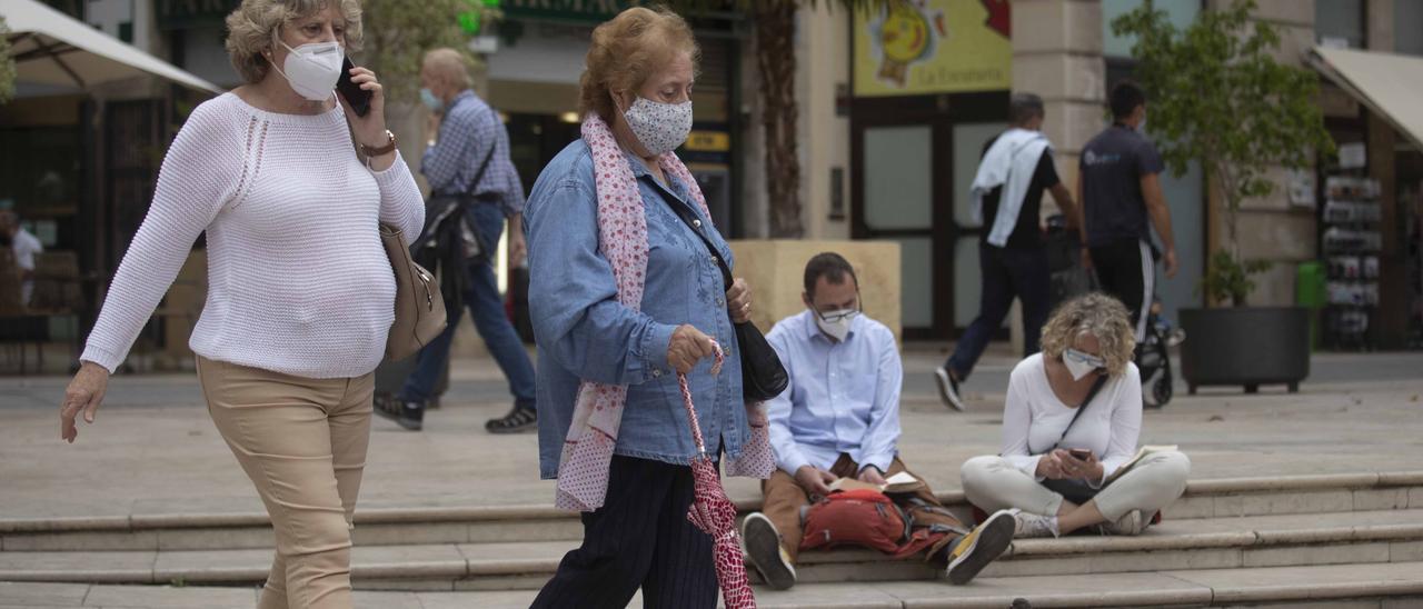 Dos mujeres pasean por la calle con mascarillas
