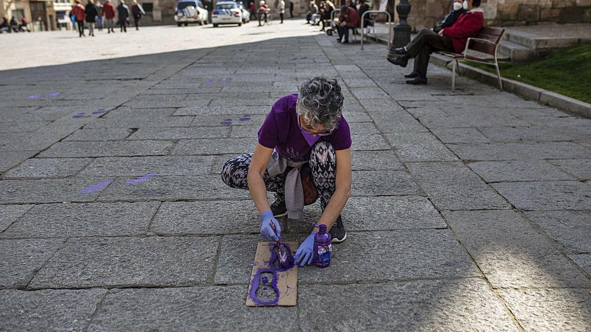 Una mujer pinta dos huellas moradas en la Plaza Mayor de Zamora