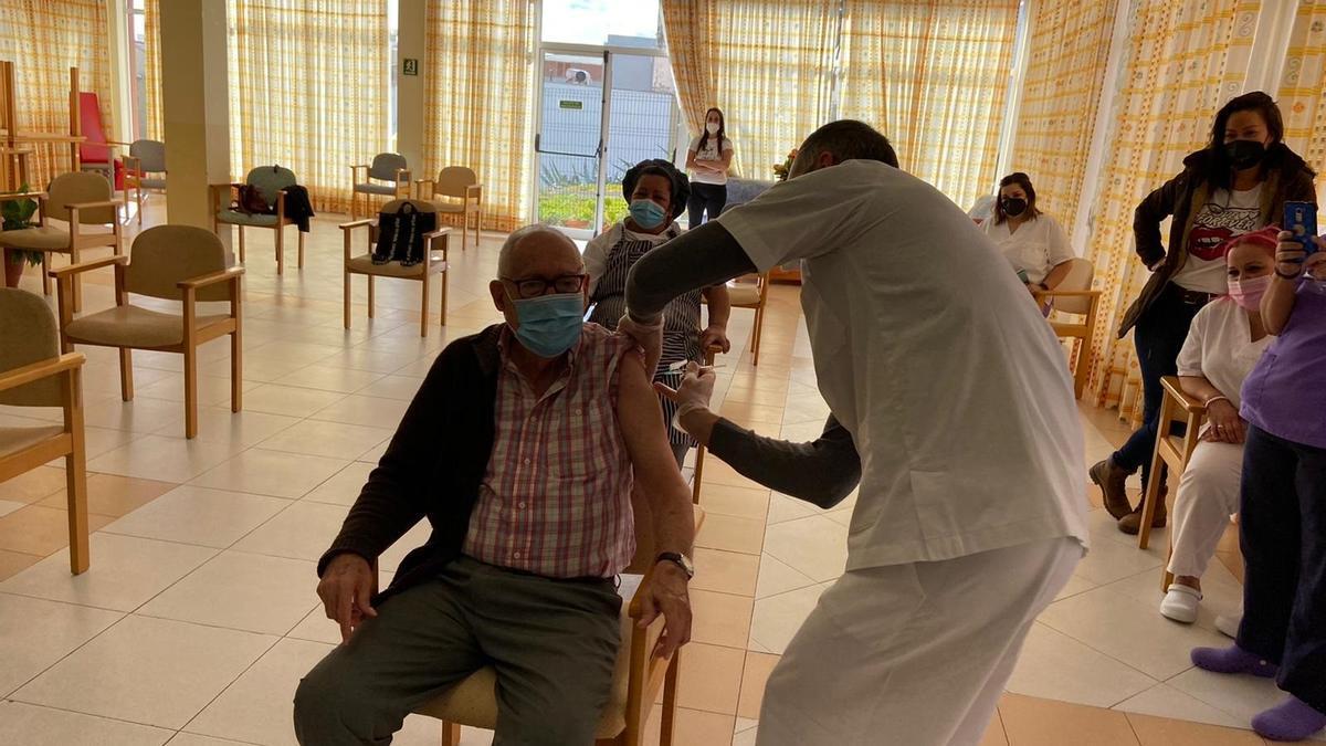 Un sanitario vacuna a una persona mayor.