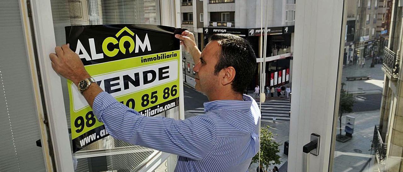 """Un agente inmobiliario coloca un cartel de """"Se Vende"""" en un piso de Vilagarcía.     // NOÉ PARGA"""