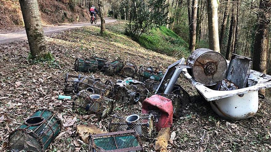 La falta de civismo siembra de residuos el monte de Coiro y los comuneros lo sanean