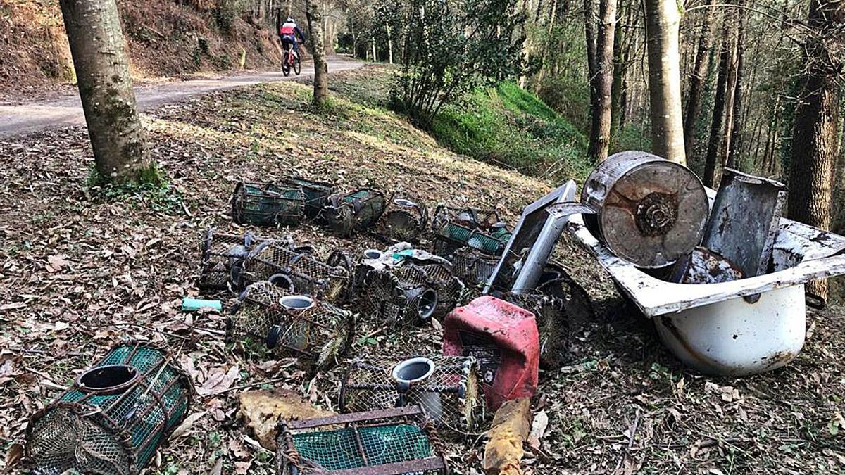 Nasas de marineros y restos de electrodomésticos junto al camino forestal. |