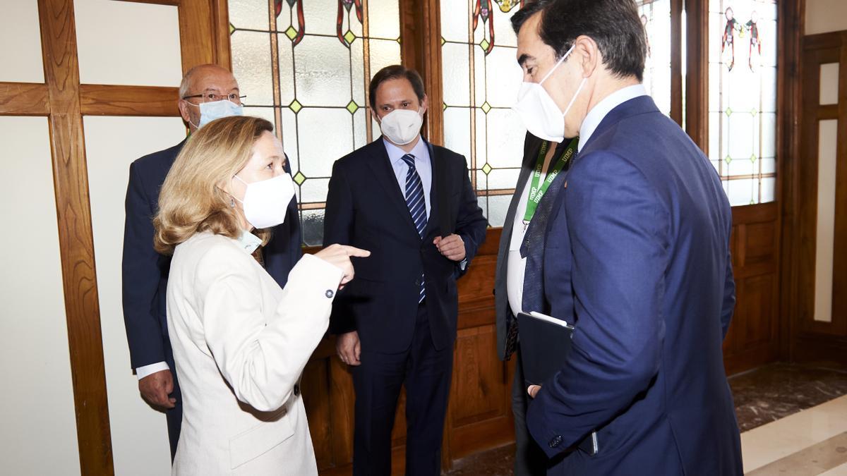 La vicepresidenta de Asuntos Económicos y Transformación Digital, Nadia Calviño (1i), y el presidente del BBVA, Carlos Torres (1d), conversan durante la inauguración del XXXVIII Seminario de la APIE 'La economía de la pandemia'
