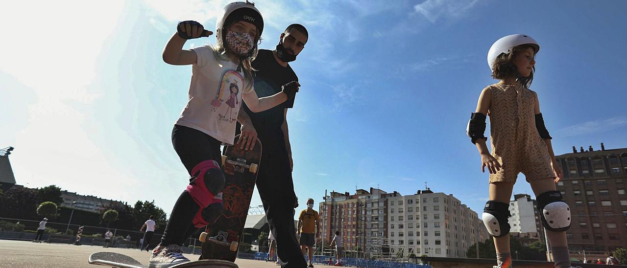 Marina Flaquer y Telma García se desplazan con sus skates ante la mirada del monitor Kike Agro.