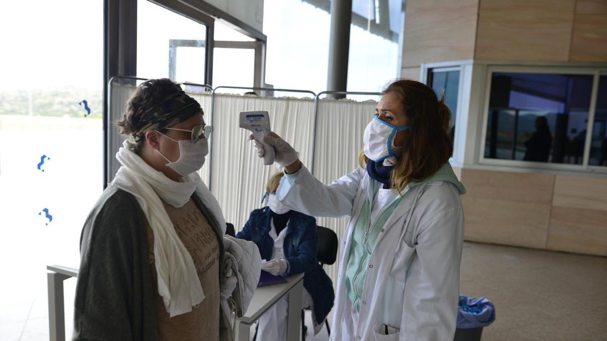 Personal del Hospital Santa Lucía de Cartagena toma la temperatura a una paciente.