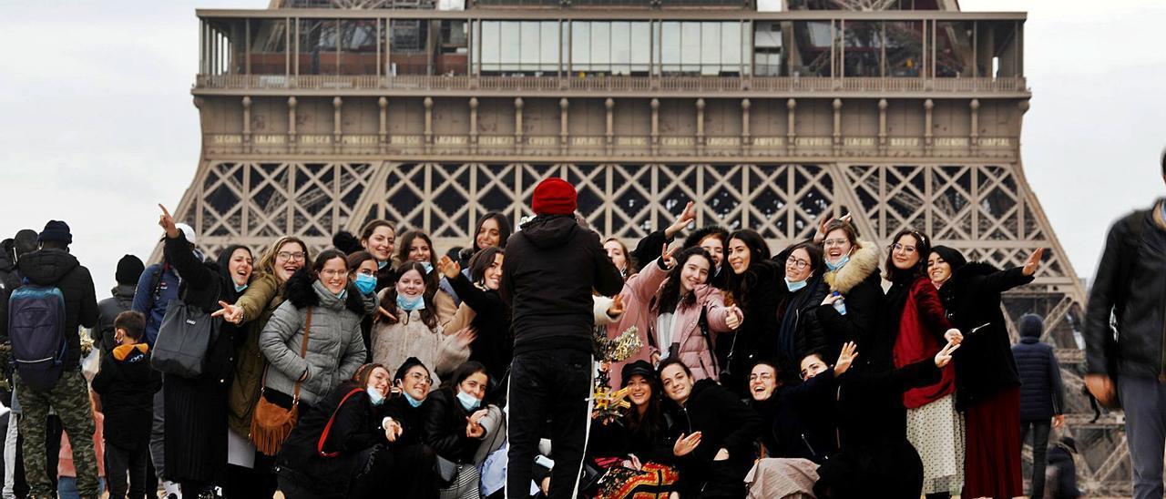 Un grupo de jóvenes, ayer, junto a la torre Eiffel, fotografiándose sin guardar la distancia social y sin mascarilla. | Reuters