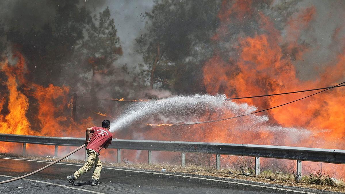 Un bomber lluita contra les flames de l'incendi que hi ha a prop de Marmaris | REUTERS/UMIT BEKTAS