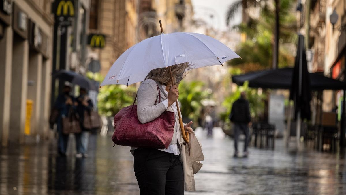 Una mujer anda bajo la lluvia.