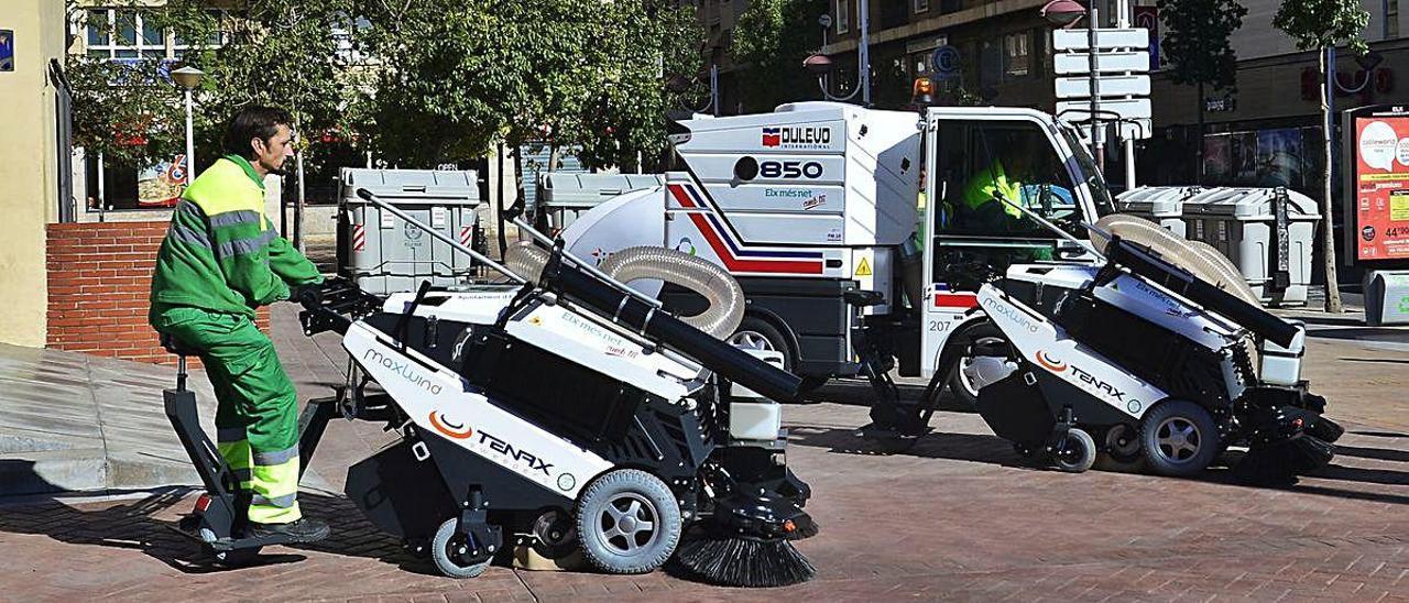 Operarios del servicio de limpieza y recogida de basuras de Elche realizan su trabajo en una de las plazas de la ciudad ilicitana.