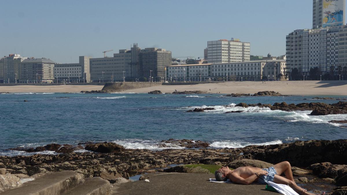 Un hombre al sol junto a la playa coruñesa de Riazor.