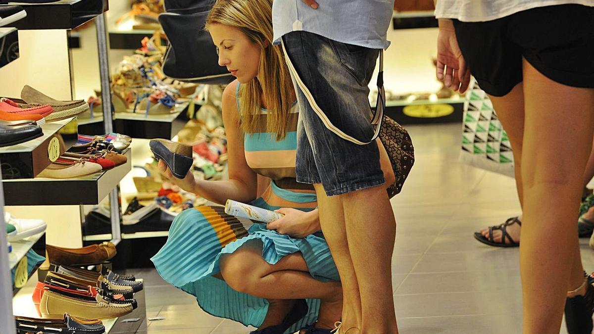 Varias clientas miran zapatos en una tienda.