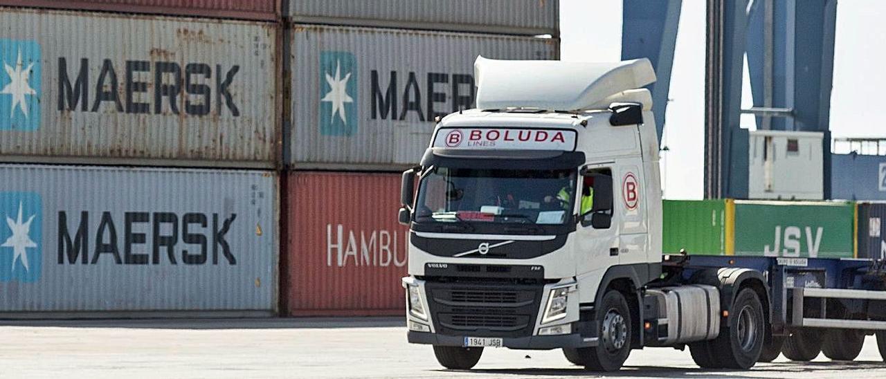 Un camión pasa junto a contenedores de carga apilados en el puerto de Alicante, ayer.