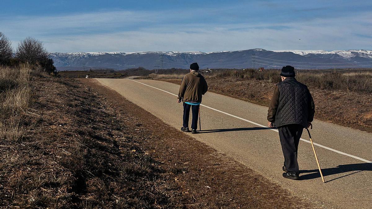 Dos hombres caminan a la salida de la localidad de Otero de Sanabria. |