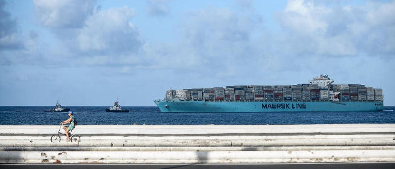 El 'Maersk Gibraltar', cuya naviera sufrió un ataque informático en junio, llega remolcado al Puerto de La Luz.