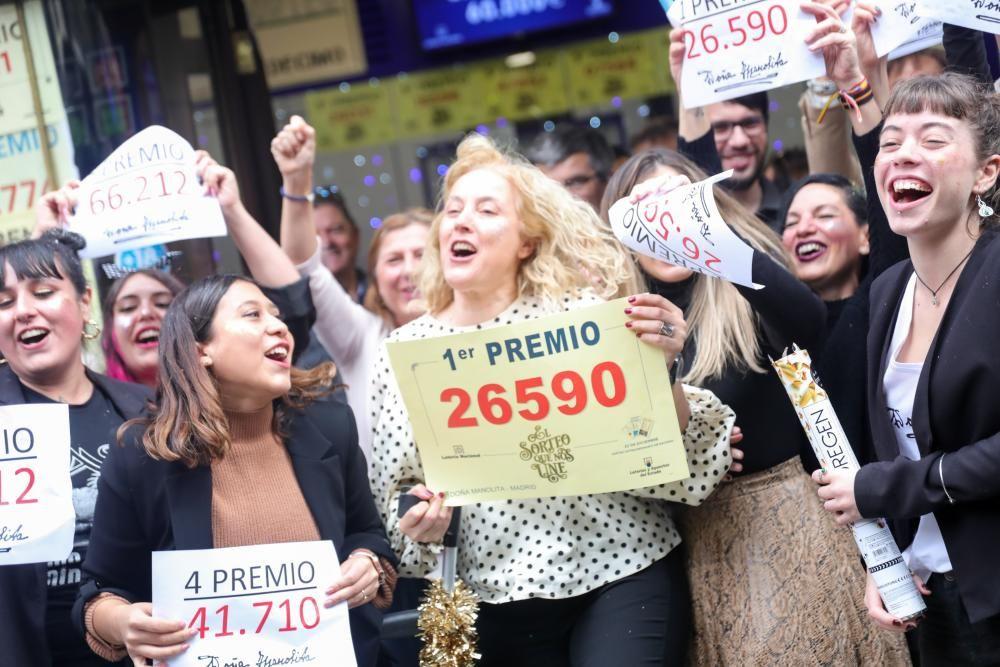 Algunos de los agraciados con distintos premios de la Lotería, frente a la famosa administración de 'Doña Manolita'.