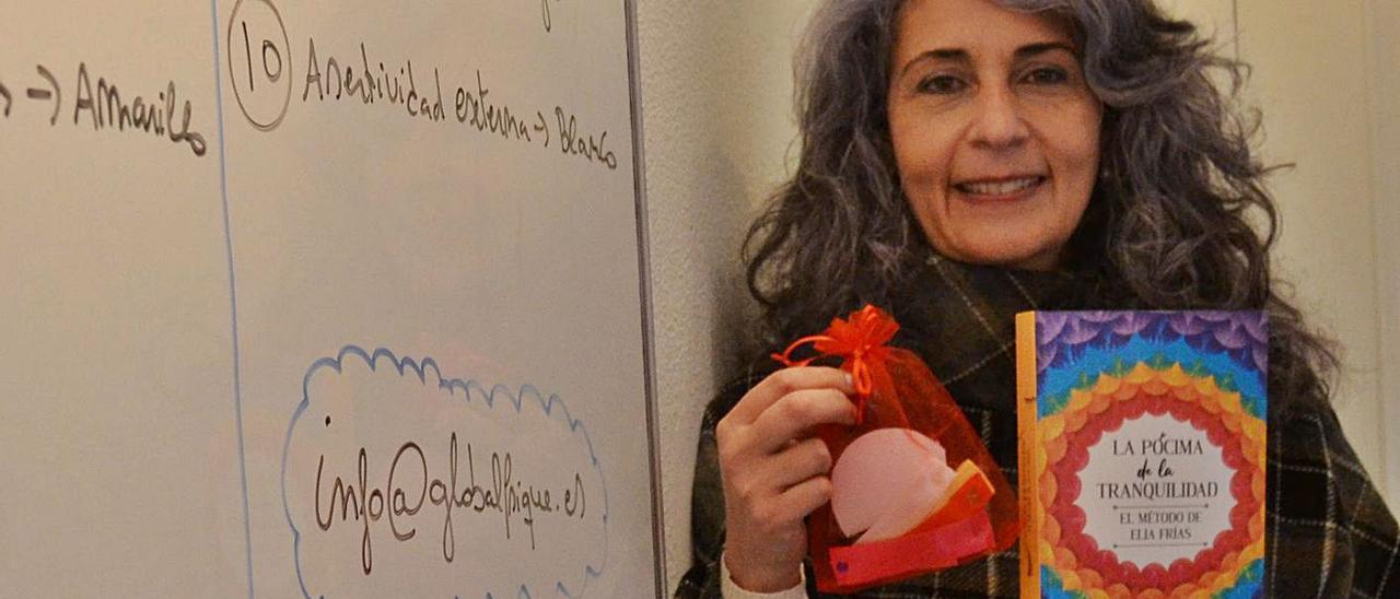 """La psicóloga Elia Frías, con su último libro y un """"kit"""" de herramientas que acompañan a la obra."""