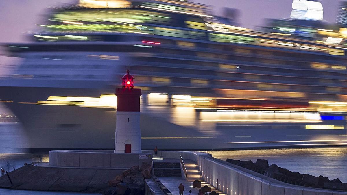 Un barco navega tras el Faro de Navidad.