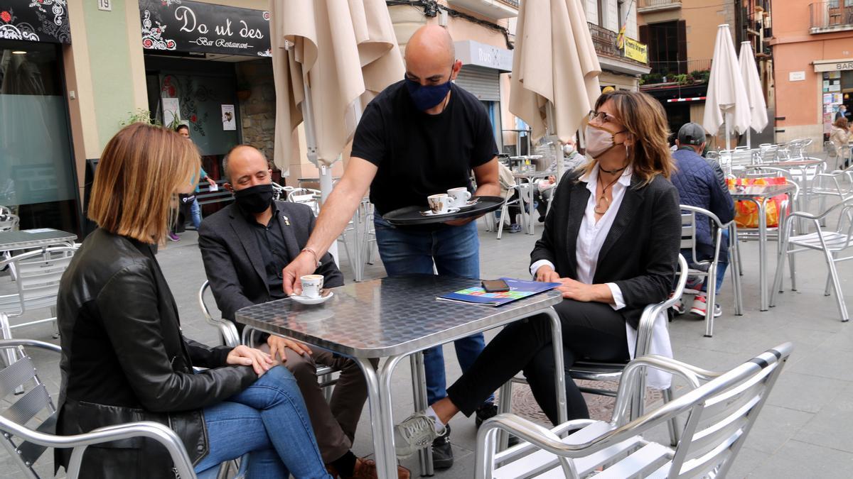 Les regidores Cristina Cruz i Núria Masgrau, amb l'alcalde de Manresa, Marc Aloy, consumint en un bar de la plaça Major de Manresa