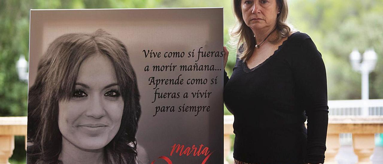 Marisol Burón posa con un retrato de su hija Marta, el día que se cumplía un año del asesinato.   DANIEL TORTAJADA