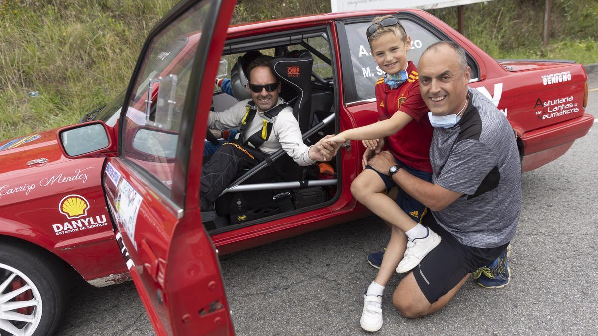 Un padre y su hijo saluda a un piloto.