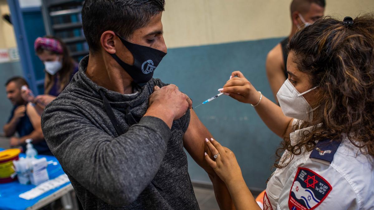 Un trabajador palestino recibe una dosis de la vacuna en un puesto de control militar de Israel.