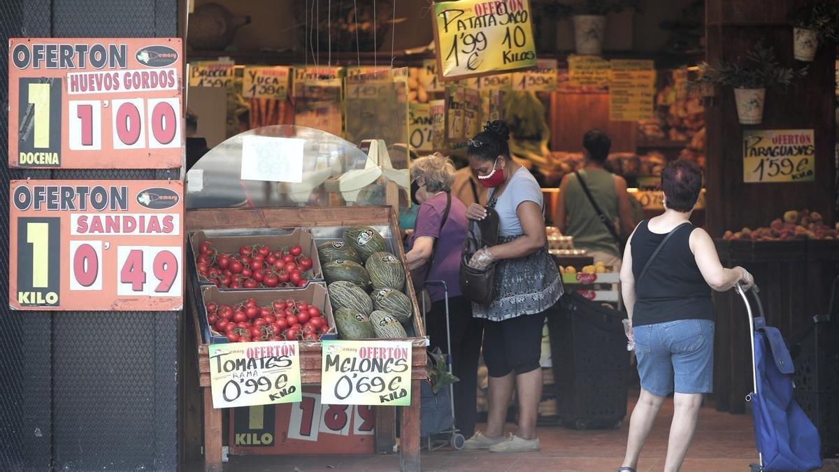 Varias personas compran en una frutería.
