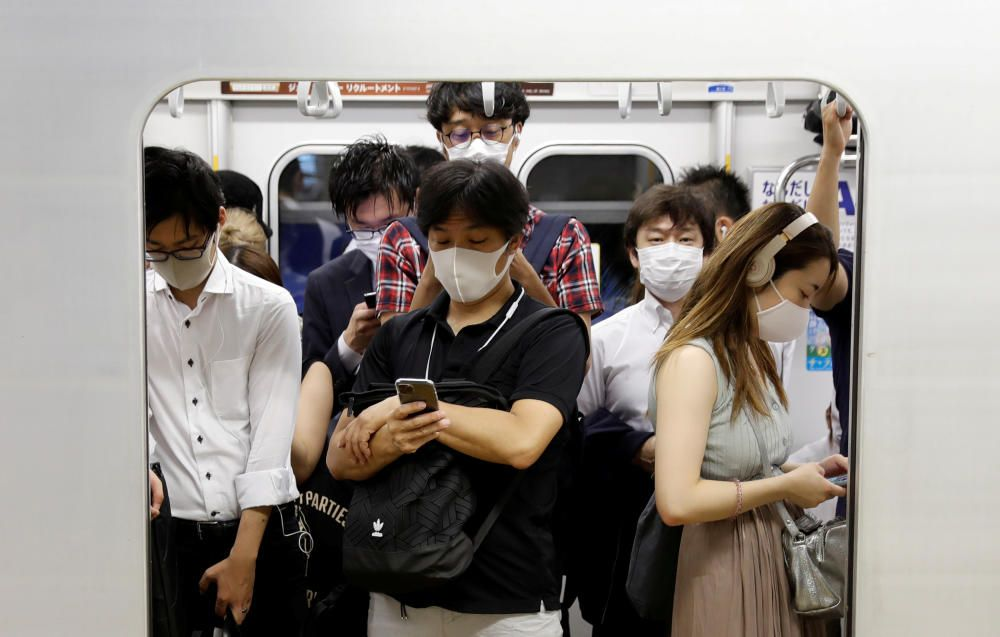 Passengers wearing protective masks amid the ...