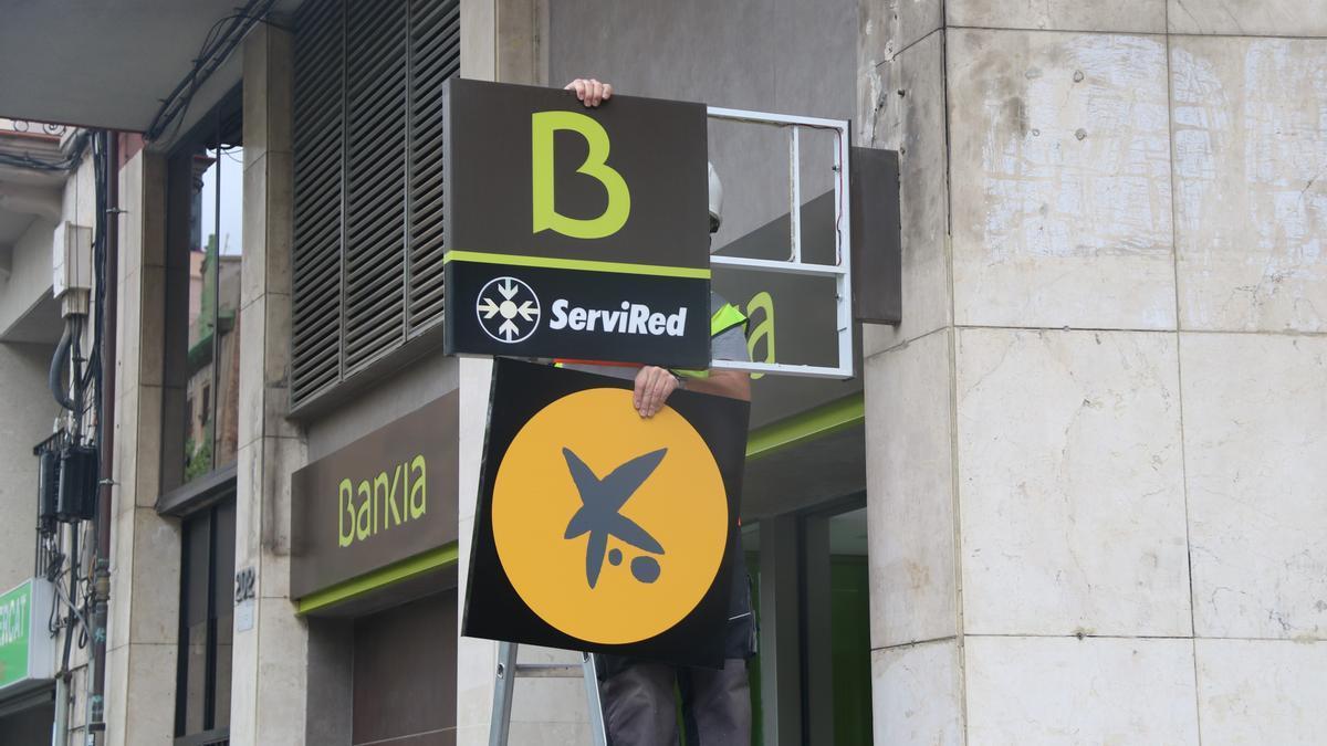 Un operario cambia el logotipo de Bankia por el de CaixaBank en una oficina.