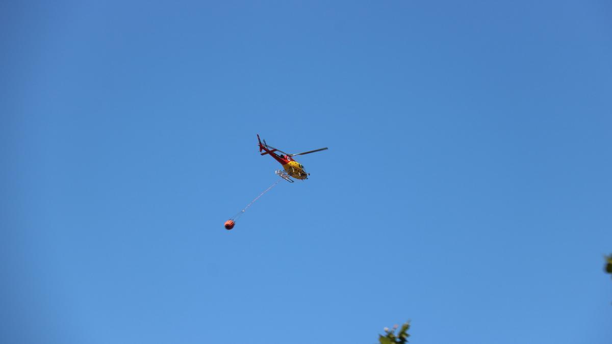 Pla mitjà d'un helicòpter treballant a l'incendi de Llançà aquest divendres 16 de juliol de 2021. (Horitzontal)