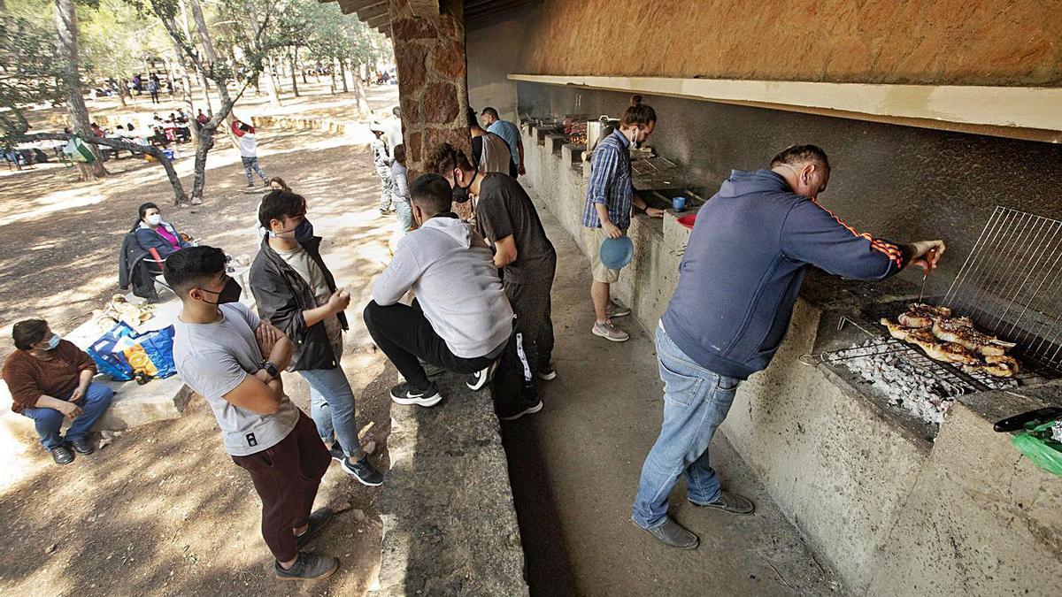 Varias personas, ayer, preparando una 'torrà' en Sant Esperit de Gilet. A la derecha, varios senderistas en la Murta de Alzira.  | D. TORTAJADA/A. PERALES IBORRA