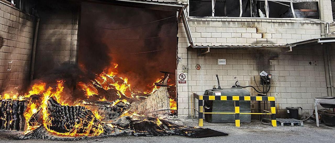 Vecinos que viven junto a la nave incendiada junto a sus viviendas del polígono Canastell. | RAFA ARJONES