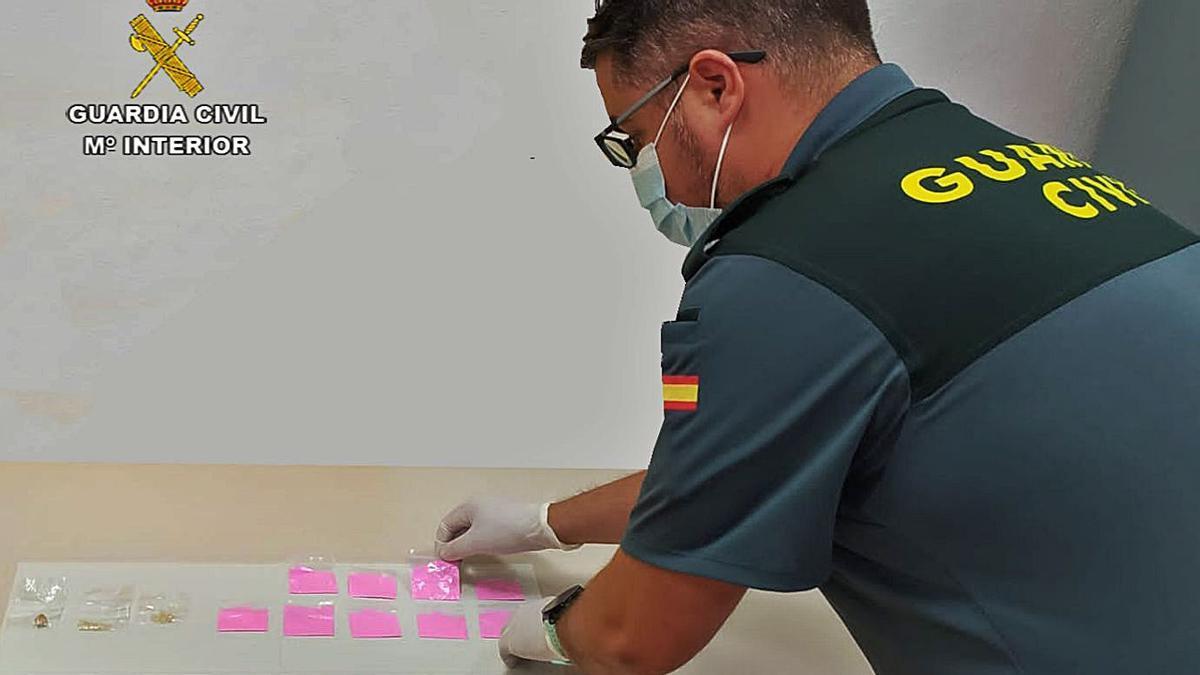 Un agente de la Guardia Civil examina las dosis de «cocaína rosa» intervenidas en Eivissa.