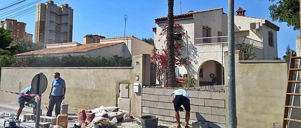 Los operarios municipales tapian la puerta de la casa.   J.A.RICO