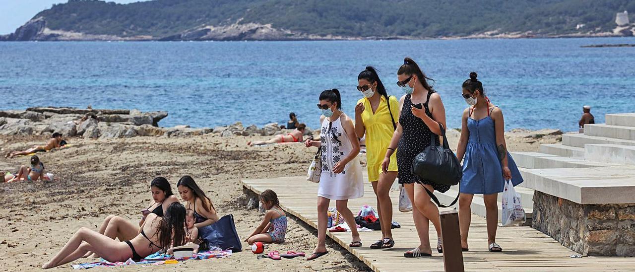 Un grupo de bañistas con mascarilla, el verano pasado en la playa de ses Figueretes.