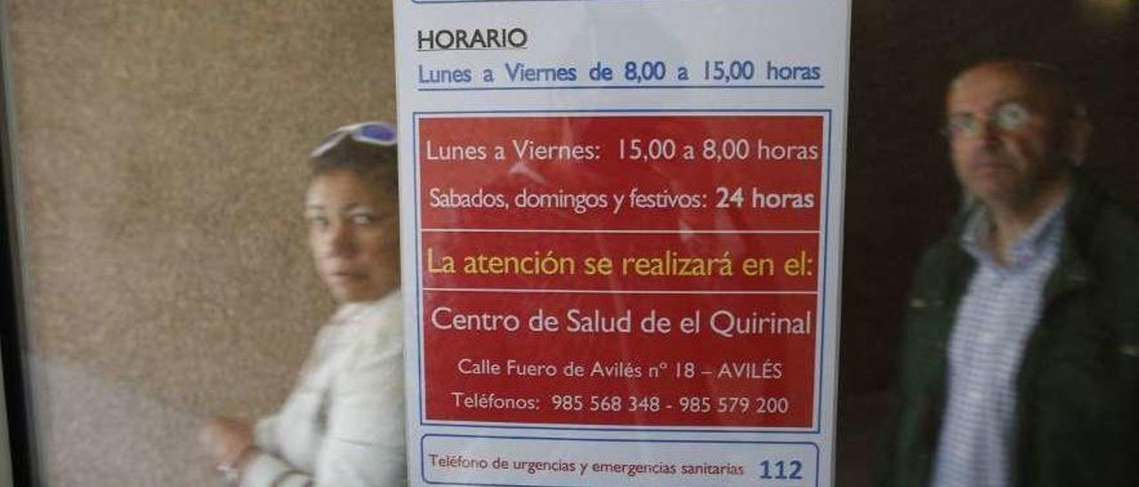 Dos usuarios del centro de salud de Sabugo pasan por detrás de un cartel que informa de los horarios de Urgencias en El Quirinal.