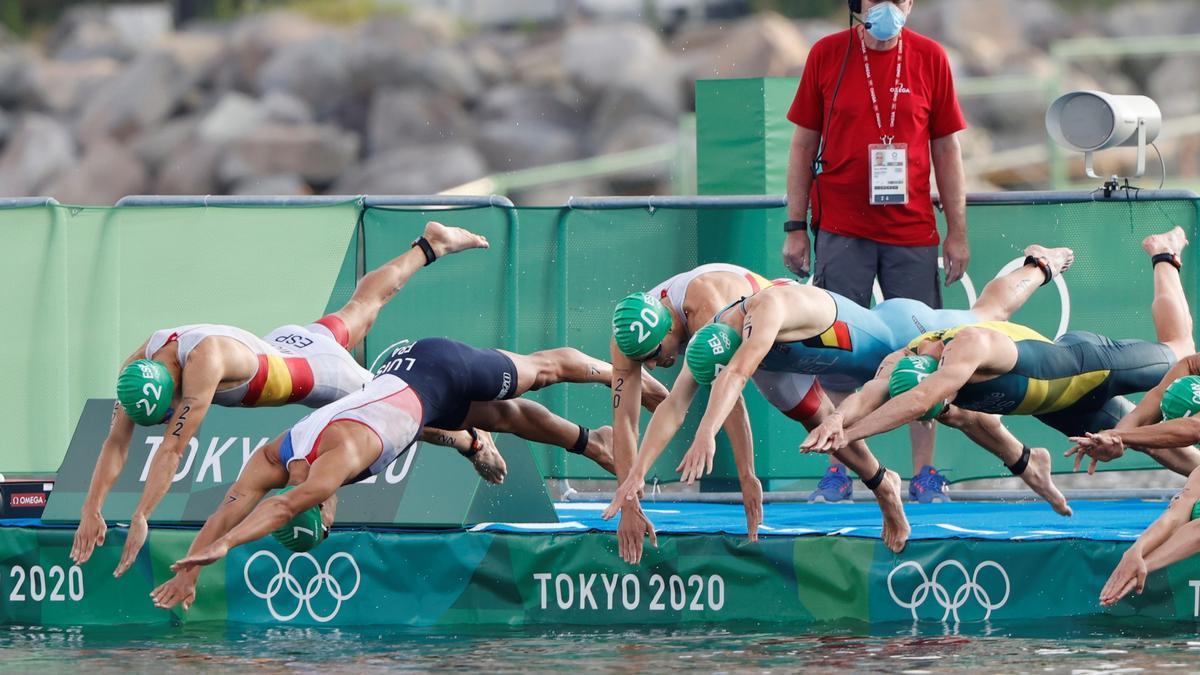 Los participantes en el triatlón saltan al agua en la primera prueba.