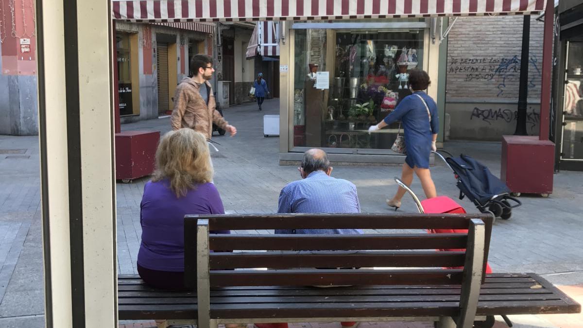 Una persona mayor, en un banco de la Plaza de las Flores.