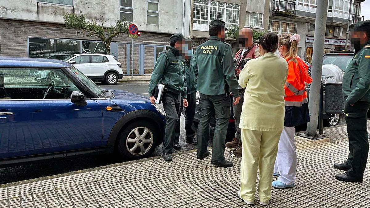 El ciudadano, ya frente al juzgado, con los agentes y personal sanitario, con el candado y la cadena sobre la acera.