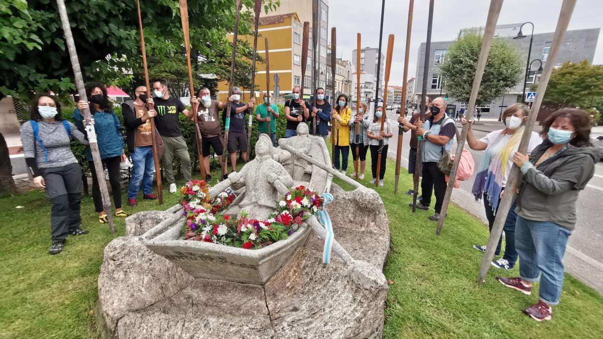 Un momento del homenaje con los remos en alto rodeando la escultura de Manuel Coia en Cangas.
