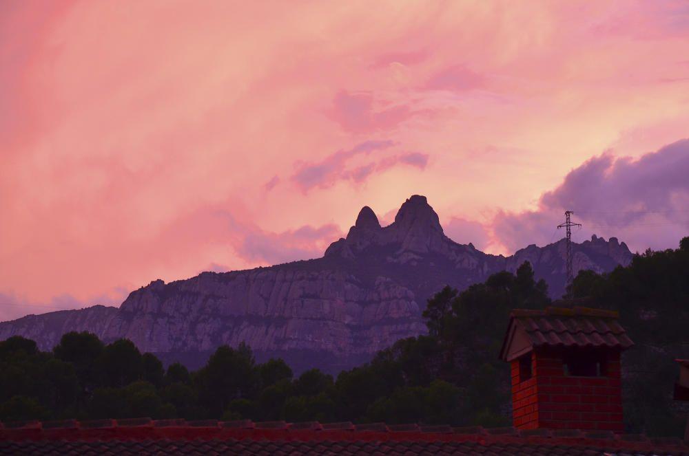 Posta de sol, núvols i Montserrat garanteixen un bonic paisatge, captat des d'una finestra.