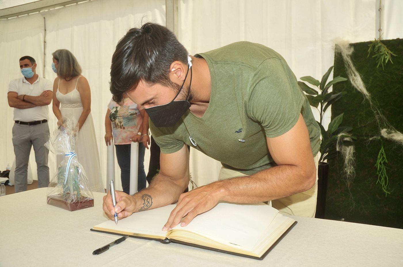 Germade firma en el libro del Concello, con el grupo Tromentelo al fondo. Rafa Vázquez.jpg