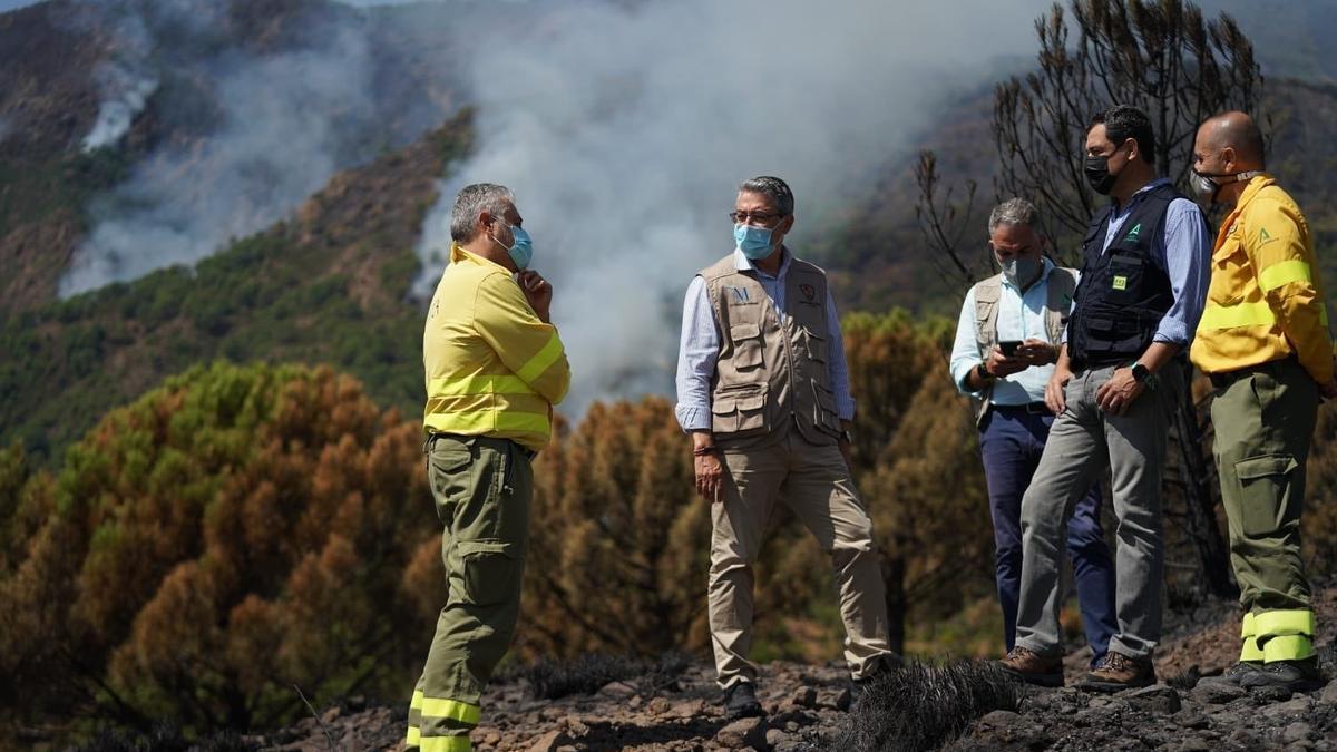 Salado, en el centro de la imagen, durante su visita el pasado sábado a zonas afectadas por el incendio forestal junto al presidente andaluz, Juanma Moreno; el consejero de Presidencia, Elías Bendodo y efectivos del Infoca.