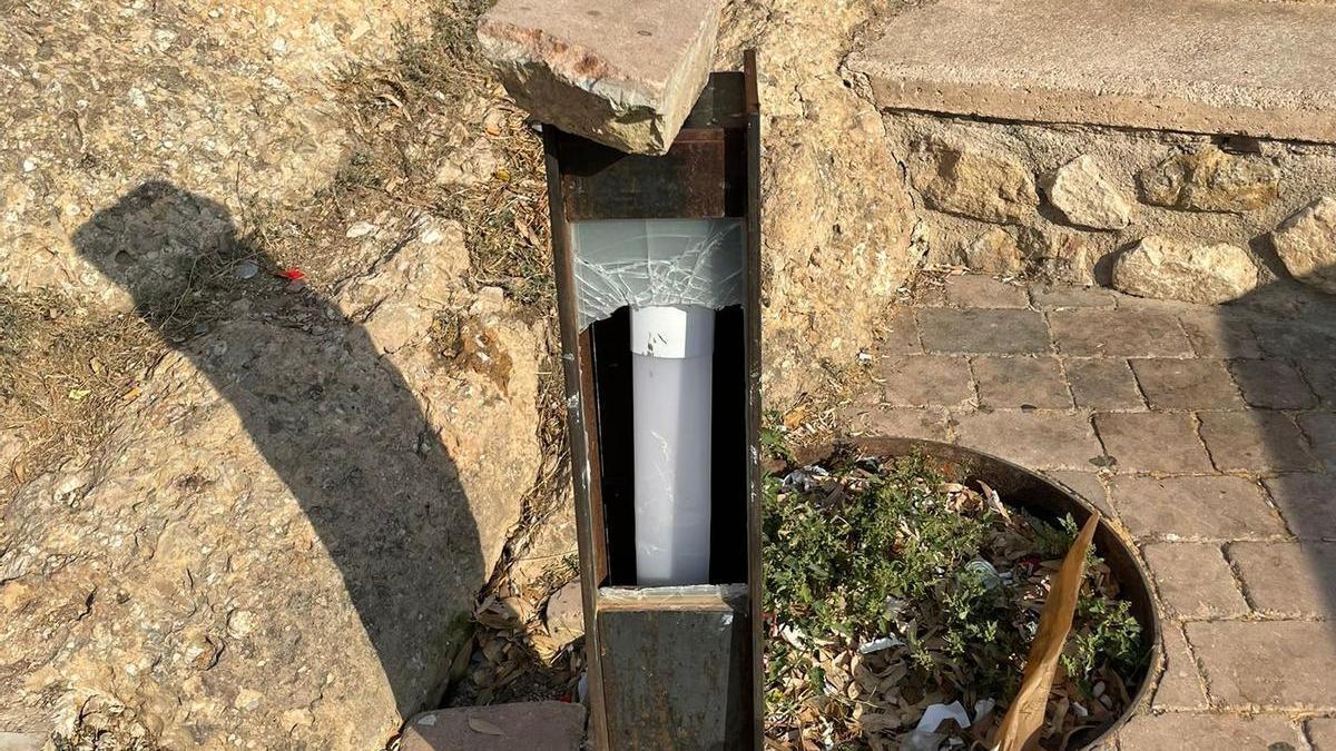 Una de las luminarias rotas con la losa que se cree utilizaron para romperla.