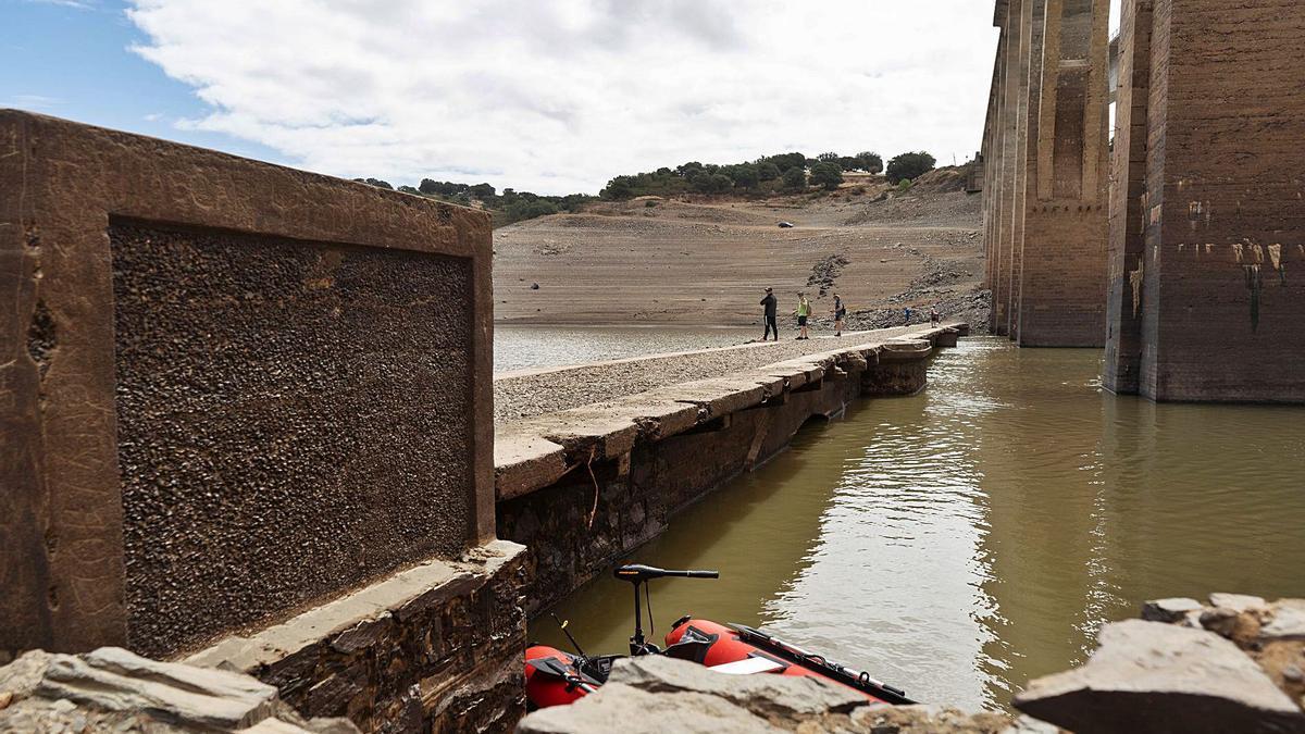 Pescadores sobre el puente viejo de Manzanal del Barco sobre el río Esla, que ha quedado al descubierto por el vaciado del embalse.   Jose Luis Fernández